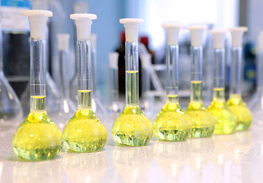 Flasks filled with yellow chemical used in chemistry experiment