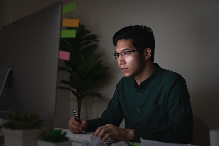 Man in STEM career doing programming on a desktop computer