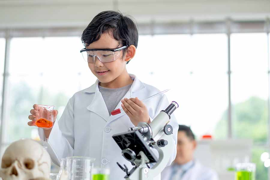 boy having fun performing chemistry experiment